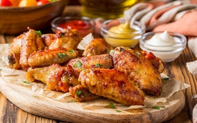 Plate of Barbecue Chicken Wings with various Dips