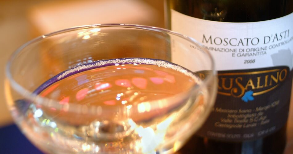 Close Up of Bottle of Moscato d'Asti and Coupé Glass filled With Sparkling Wine