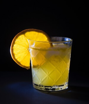 Rock Glass filled with a Yellow Cocktail