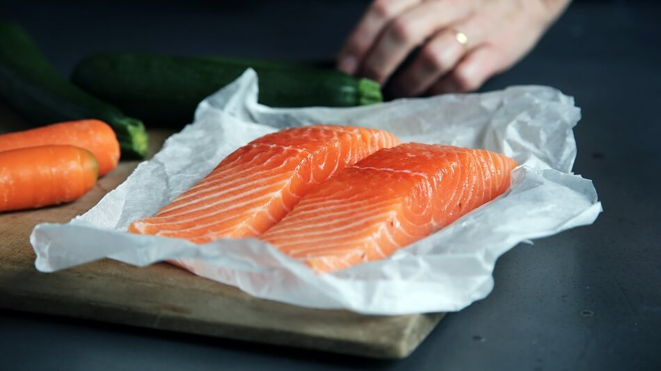 Two Thick Slices of Raw Salmon on a Wooden Board with Carrots and Cucumber