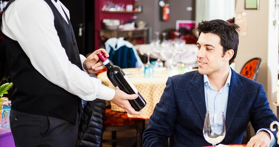 Waiter Presents Red Wine Bottle to Patron