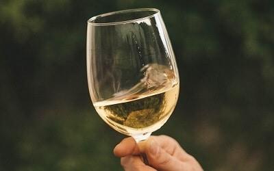 Man Swirling White Wine