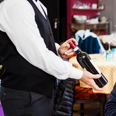 Sommelier Presenting a Bottle of Wine to a Patron
